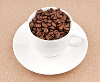 Cup with coffee beans. On textured background royalty free stock image