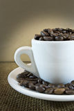 Cup with coffee beans. White cup with coffee beans on brown background Stock Photo
