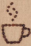 A cup of coffee beans. A cup of coffee beans with smoke on the background of burlap Stock Images