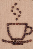 A cup of coffee beans. A cup of coffee beans with smoke on the background of burlap Stock Image