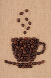 A cup of coffee beans. A cup of coffee beans with smoke on the background of burlap Stock Photos