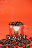 Cup of coffee beans. On red background Royalty Free Stock Photography