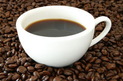 Cup of coffee and beans. A still life of a cup of coffee and whole coffee beans royalty free stock photos