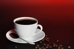Cup of coffee with beans. Full cup of black coffee with scattered beans, crimson background Stock Image