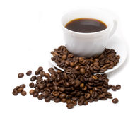The cup of coffee and beans 3. The cup of coffee and coffee beans scattered around Royalty Free Stock Images