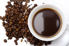 The cup of coffee and beans. The cup of coffee and coffee beans scattered around Royalty Free Stock Image