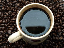 Cup of coffee with beans. A cup of fresh black coffee sits on top a pile of coffee beans stock photo