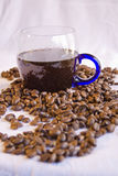 Cup of Coffee and beans. Hot cup of coffee in glass mug with whole beans and white background Royalty Free Stock Images