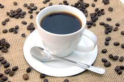 Cup with coffee beans. A shot of a with cup on brown coffee beans Royalty Free Stock Image