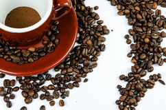 Cup of coffee with beans from above on white background Royalty Free Stock Photos