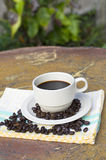 Cup of coffee and beans. On background of a plant Royalty Free Stock Images