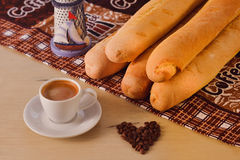 Cup of coffee with beans and baguette Stock Photography