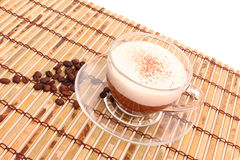 Cup of coffee and beans on bamboo mat Royalty Free Stock Image
