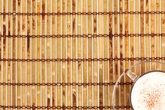 Cup of coffee and beans on bamboo mat Royalty Free Stock Photography