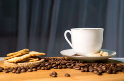 Cup of coffee, beans and biscuits. A cup of coffee, beans, biscuits, lambs of sugar, on a wooden table stock photo