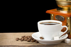 Cup of coffee and beans on black. Background stock photography