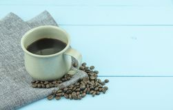 Cup of coffee with coffee beans on blue color wooden background. stock photos