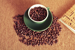 Cup of coffee beans and a book Royalty Free Stock Photos