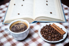 Cup of coffee with beans and book on the tablecloth closeup. Cup of coffee with beans on a plate and book on the tablecloth closeup Stock Image
