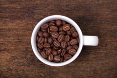 Cup of coffee beans on the brown wooden background Royalty Free Stock Image