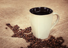 Cup of coffee and beans on burlap background Royalty Free Stock Images