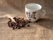 Cup of coffee and beans on burlap sack royalty free stock images