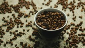 Cup of coffee beans on canvas. Closeup of small brown cup filled with roasted coffee beans on burlap textile with beans around stock video footage