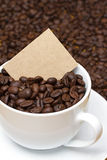 Cup of coffee beans with card Stock Image