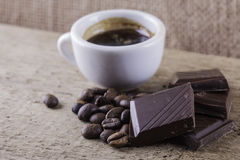 Cup, coffee beans, chocolate wooden board closeup top view background Stock Photo