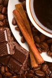 Cup of coffee, beans, cinnamon and black chocolate Royalty Free Stock Photos
