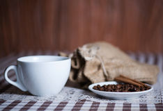 Cup and coffee beans with cinnamon on a plate next to sack Royalty Free Stock Photos