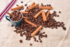 Cup with coffee beans cinnamon stick on jute background. Morning Stock Photo