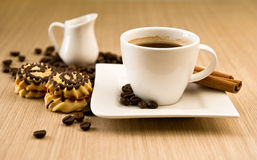 Cup of coffee with beans and cinnamon sticks Stock Photography