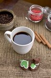 A cup of coffee, coffee beans, cinnamon sticks, a sweet chocolate ingredient in a jar. A cup of coffee, coffee beans, cinnamon sticks, a sweet chocolate Royalty Free Stock Photos
