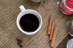 A cup of coffee, coffee beans, cinnamon sticks, a sweet chocolate ingredient in a jar. A cup of coffee, coffee beans, cinnamon sticks, a sweet chocolate Stock Photography