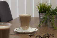 Cup Of Coffee And Beans. A clear glass coffee cup on a saucer with coffee beans on the table Royalty Free Stock Images