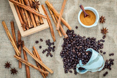 The Cup of coffee beans on the cloth sack with cinnamon sticks , Royalty Free Stock Photography
