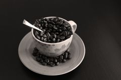 Cup of coffee with beans. Coffee beans in a cup of coffee, black background, copyspace stock image