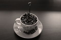 Cup of coffee with beans. Coffee beans in a cup of coffee, black background, copyspace stock photography