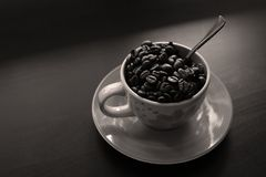 Cup of coffee with beans. Coffee beans in a cup of coffee, black background, copyspace royalty free stock image