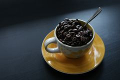 Cup of coffee with beans. Coffee beans in a cup of coffee, black background, copyspace royalty free stock photo