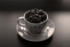 Cup of coffee with beans. Coffee beans in a yellow cup of coffee, black background, copyspace royalty free stock photo