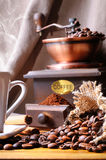 Cup of coffee, beans and coffee grinder close up Royalty Free Stock Photo