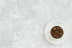 Cup with coffee beans on concrete background. royalty free stock photography