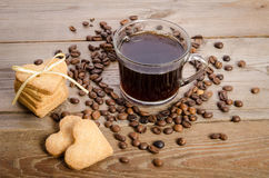 Cup of coffee, beans and cookies-hearts related together. The cup of coffee, coffee beans and cookies-hearts related together on  wooden table Stock Image