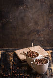 Cup with coffee beans at dark wooden background Royalty Free Stock Images