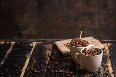 Cup with coffee beans at dark wooden background Royalty Free Stock Photo