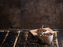 Cup with coffee beans at dark wooden background Stock Images