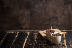 Cup with coffee beans at dark wooden background Royalty Free Stock Photos