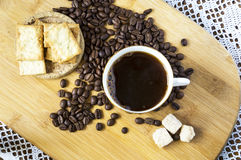 Cup of coffee and beans on a desk. A cup of coffee, beans, biscuits, lambs of sugar, on a wooden desk stock images